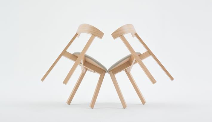 Dwa krzesła z kolekcji UXI opierające się o siebie