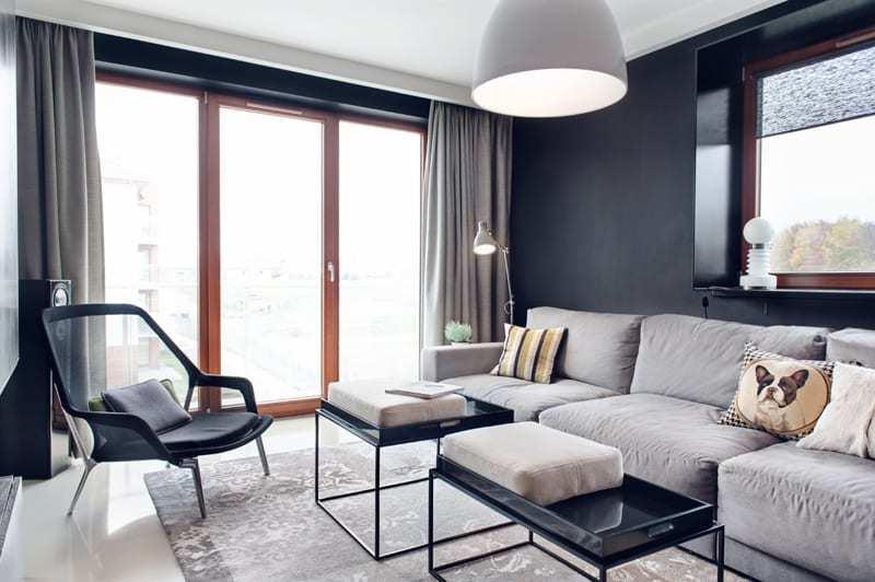 Salon z dużym oknem i szarą ścianąw apartamencie projektu pracowni formativ