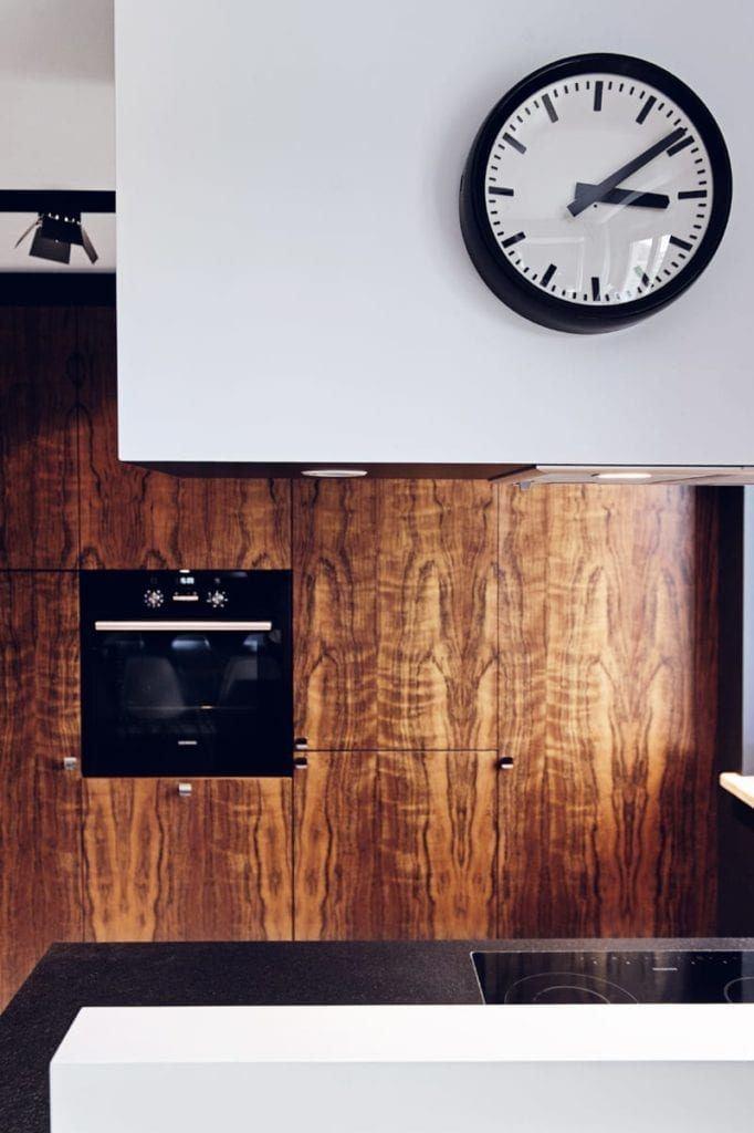 Kuchnia z brązową ścianą i jasną podłogąw apartamencie projektu pracowni formativ