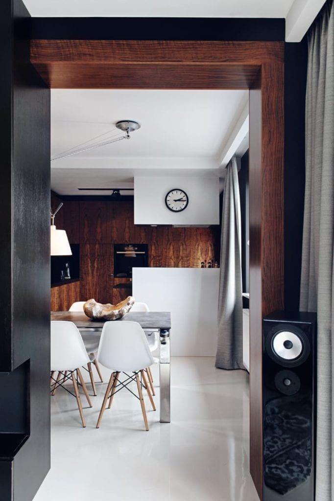 Brązowa ściana w kuchni i zegar na ścianie w apartamencie projektu pracowni formativ