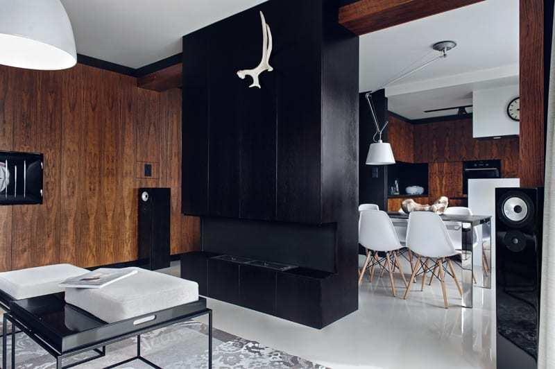 Salon z brązową ścianą i jasną podłogąw apartamencie projektu pracowni formativ