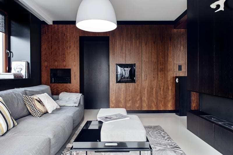 Salon z brązową ścianą i czarnymi drzwiamiw apartamencie projektu pracowni formativ