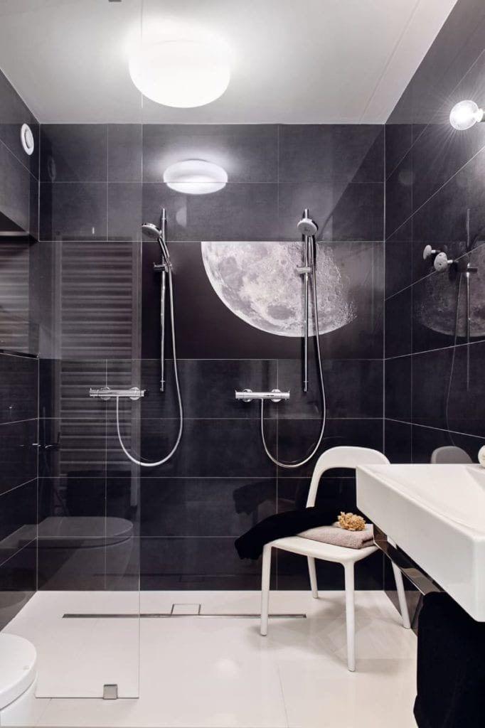 Łazienka z czarnymi płytkami i jasną podłogąw apartamencie projektu pracowni formativ