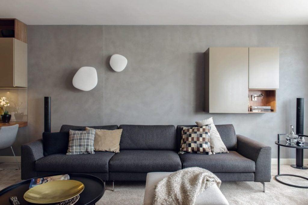 Niebieska sofa w salonie z szarą ścianą w gdyńskim mieszkaniu projektu pracowni formativ