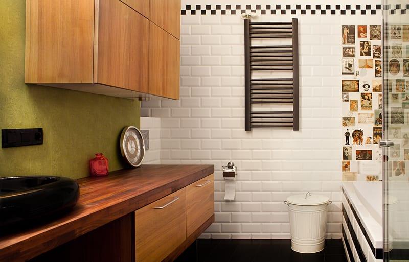 Biała łazienka, czary grzejnik i zielona ściana
