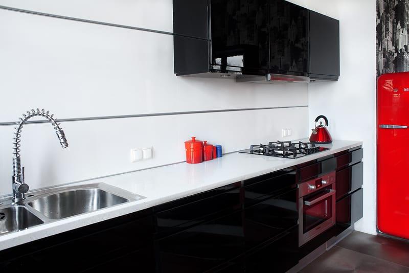 Biała kuchnia, czarne meble i czerwone akcenty
