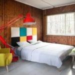 Pokój dzienny i czerwona lampa kreślarska stojąca przy ścianie