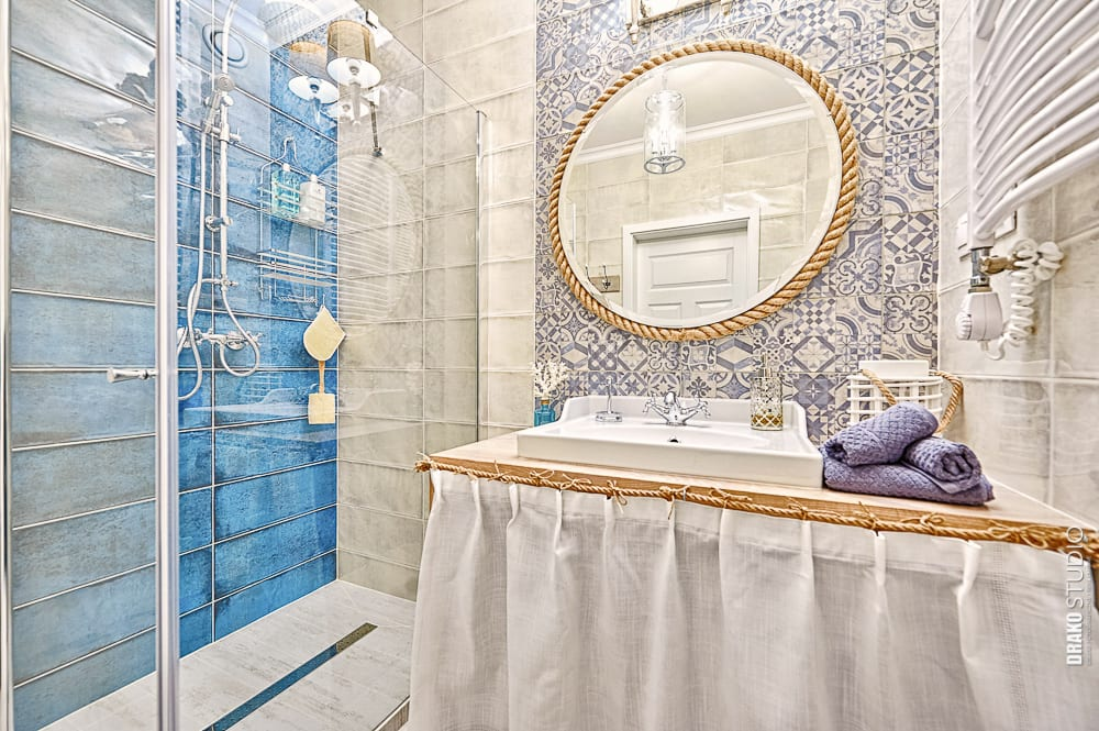 Łazienka w stylu Hampton. Duże lustro i niebieskie płytki na ścianie.