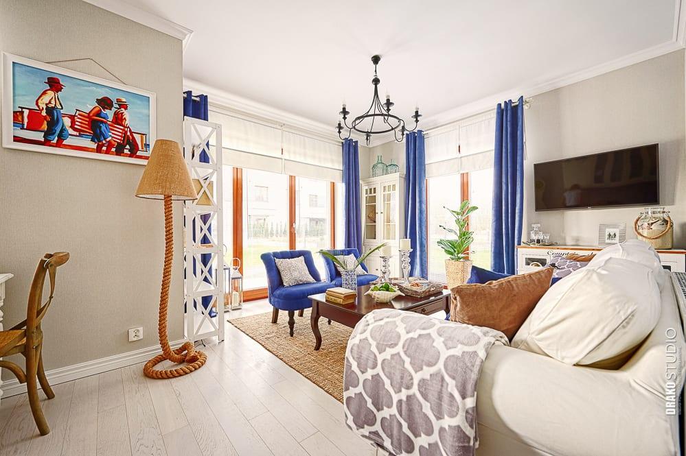 Apartament w stylu marynistycznym. Hampton. Niebieskie zasłony w salonie.
