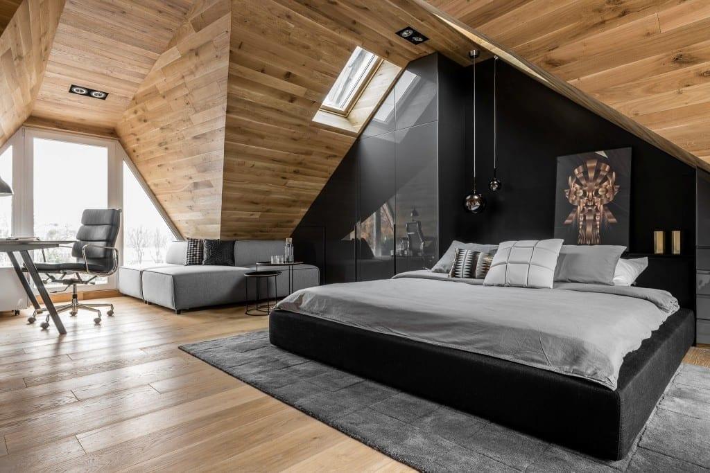 Sypialnia na poddaszu projektu pracowni Raca Architekci - duże łóżko, czarna ściana i drewno na suficie