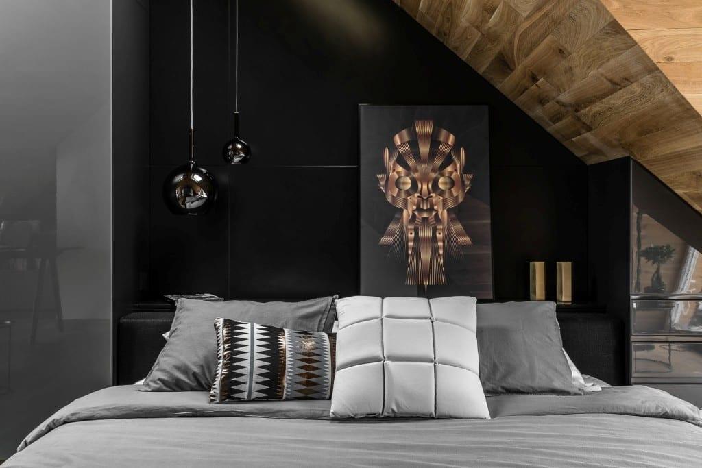 Sypialnia na poddaszu projektu pracowni Raca Architekci - czarna ściana i łóżko z szarą pościelą