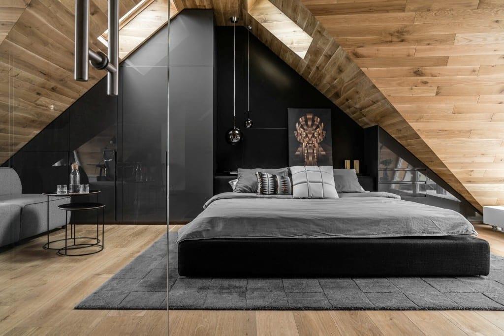 Sypialnia na poddaszu projektu pracowni Raca Architekci - duże łóżko stojące pod ścianą