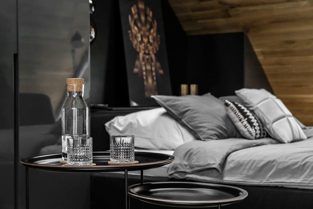 Sypialnia na poddaszu projektu pracowni Raca Architekci - stolik stojący przy łóżku