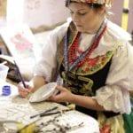 Kobieta w ludowym stroju malująca talerz