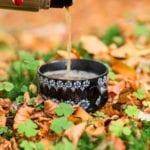 Nalewanie herbaty z termosu do czarnej filiżanki