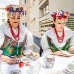 Dwie kobiety w ludowych strojach malują porcelanę