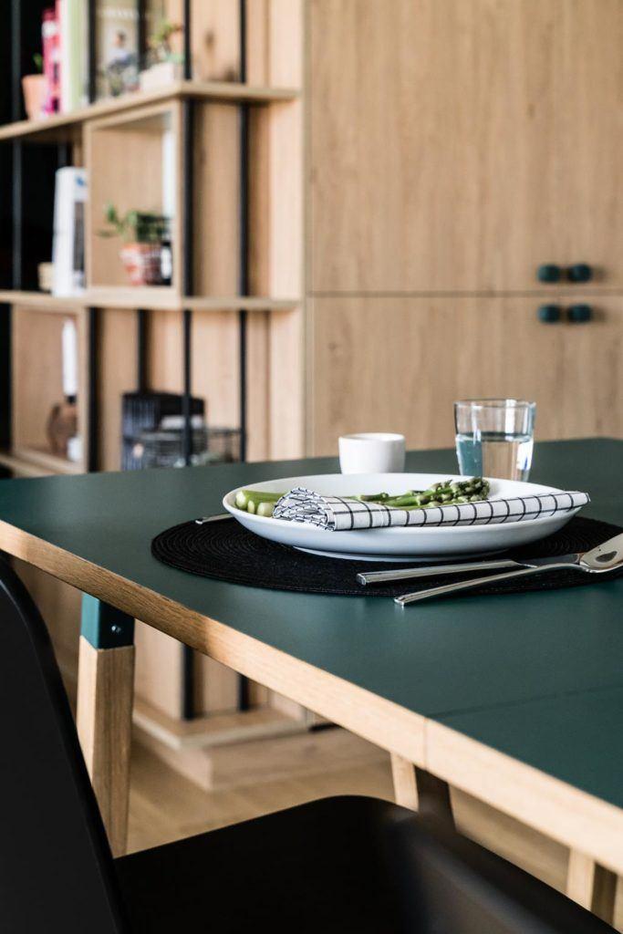 Nowoczesne i przytulne mieszkanie dla pary i stół z zielonym blatem w kuchni
