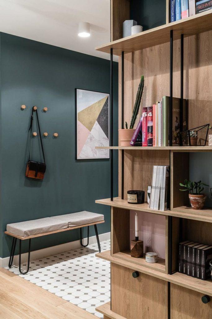 Ściana w zielonym, butelkowym kolorze w przedpokoju w nowoczesnym i przytulnym mieszkaniu projektu Reca Architekci