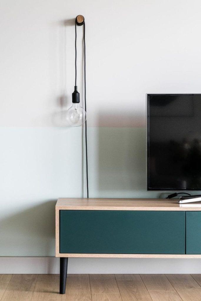 Komoda z frontami w zielonym kolorze w nowoczesnym i przytulnym mieszkaniu projektu Reca Architekci