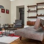 Piękne mieszkanie w zabytkowej kamienicy projektu Loft Kolasiński. Duży salon z regałem stojącym przy ścianie.