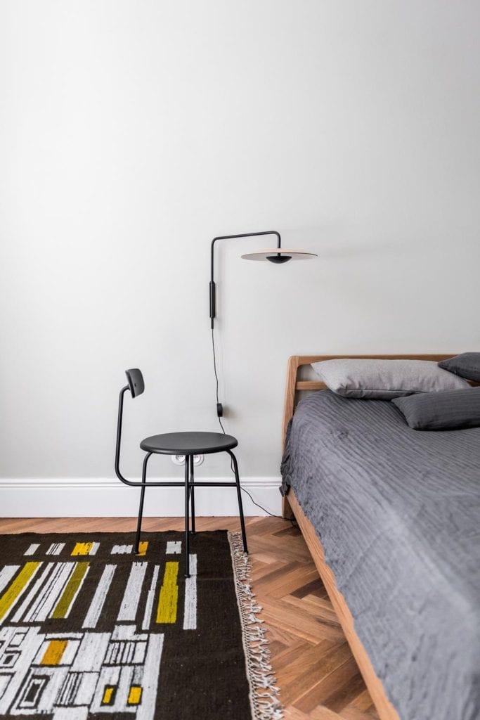 Piękne mieszkanie w zabytkowej kamienicy projektu Loft Kolasiński. Stolik nocny stojący przy łóżku w sypialni.
