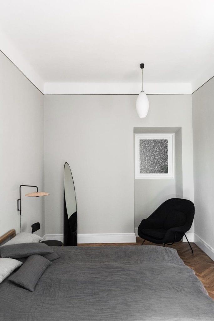 Piękne mieszkanie w zabytkowej kamienicy projektu Loft Kolasiński. Sypialnia i piękne lustro stojące przy ścianie.