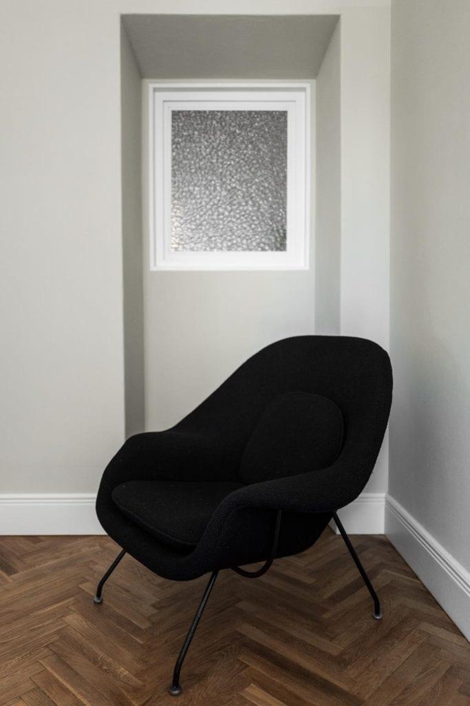 Piękne mieszkanie w zabytkowej kamienicy projektu Loft Kolasiński. Ciemny fotel stojący przy ścianie w sypialni.