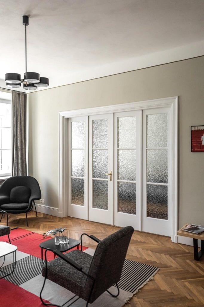 Piękne mieszkanie w zabytkowej kamienicy projektu Loft Kolasiński. Piękne, duże, białe drzwi dzielące salon i sypialnie.