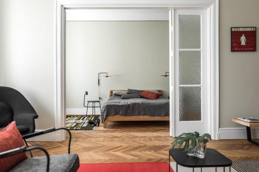 Piękne mieszkanie w zabytkowej kamienicy projektu Loft Kolasiński. Duże drzwi dzielące salon i sypialnie w kamienicy.