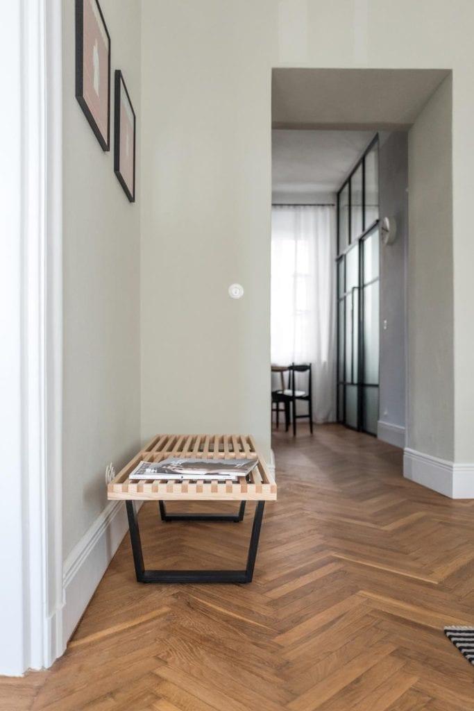 Piękne mieszkanie w zabytkowej kamienicy projektu Loft Kolasiński. Duży przedpokój z drewnianą ławką.