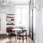 Piękne mieszkanie w zabytkowej kamienicy projektu Loft Kolasiński. Obszerna kuchnia, drewniany stół i trzy krzesła.