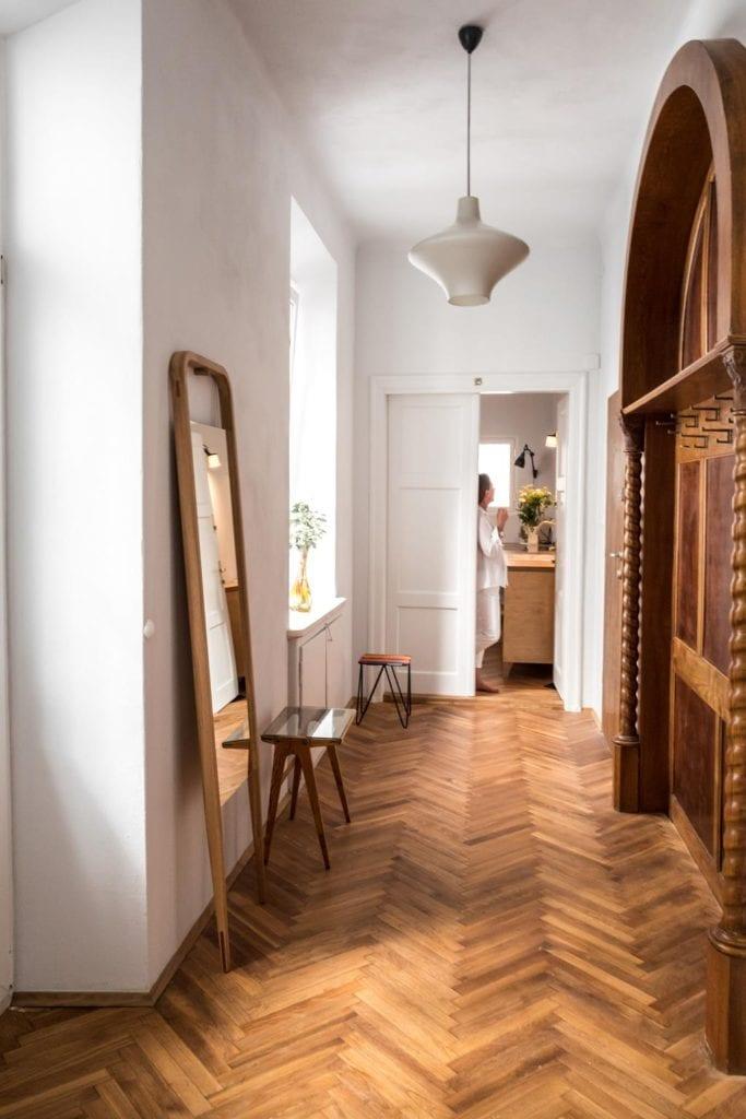 Piękne mieszkanie w zabytkowej kamienicy projektu Loft Kolasiński. Przedpokój z drewnianymi elementami.