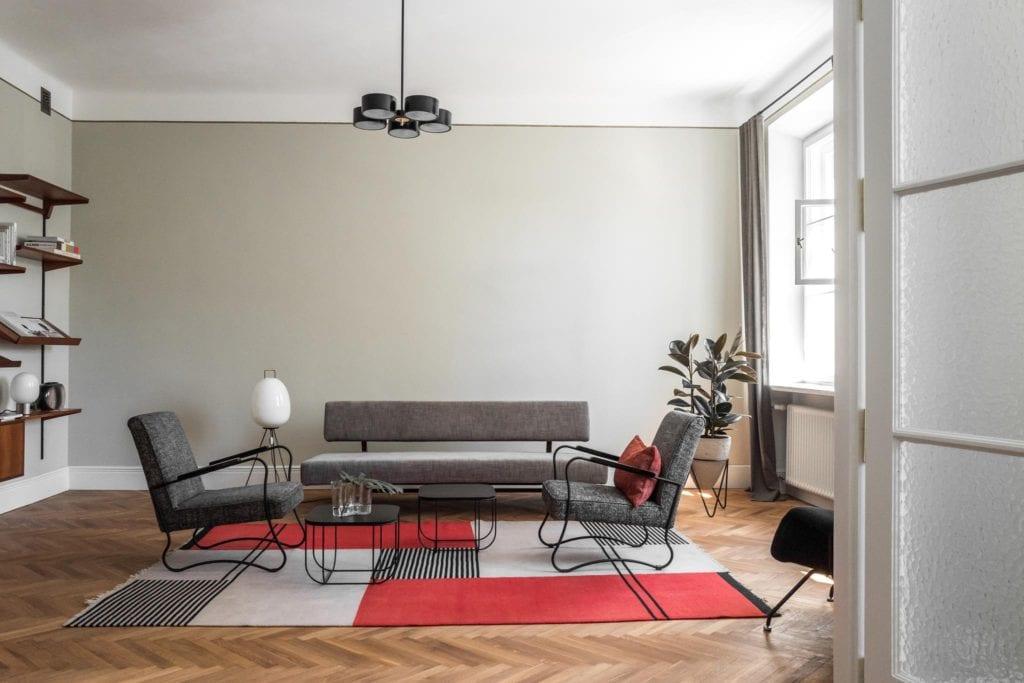 Piękne mieszkanie w zabytkowej kamienicy projektu Loft Kolasiński. Duży, wysoki salon, szare meble i dywan z czerwonym detalem.
