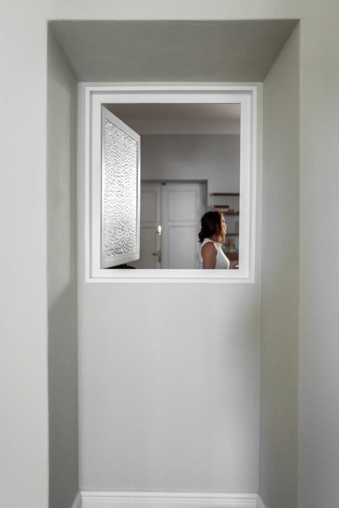 Piękne mieszkanie w zabytkowej kamienicy projektu Loft Kolasiński. Okno dzielące dwa pomieszczenia.