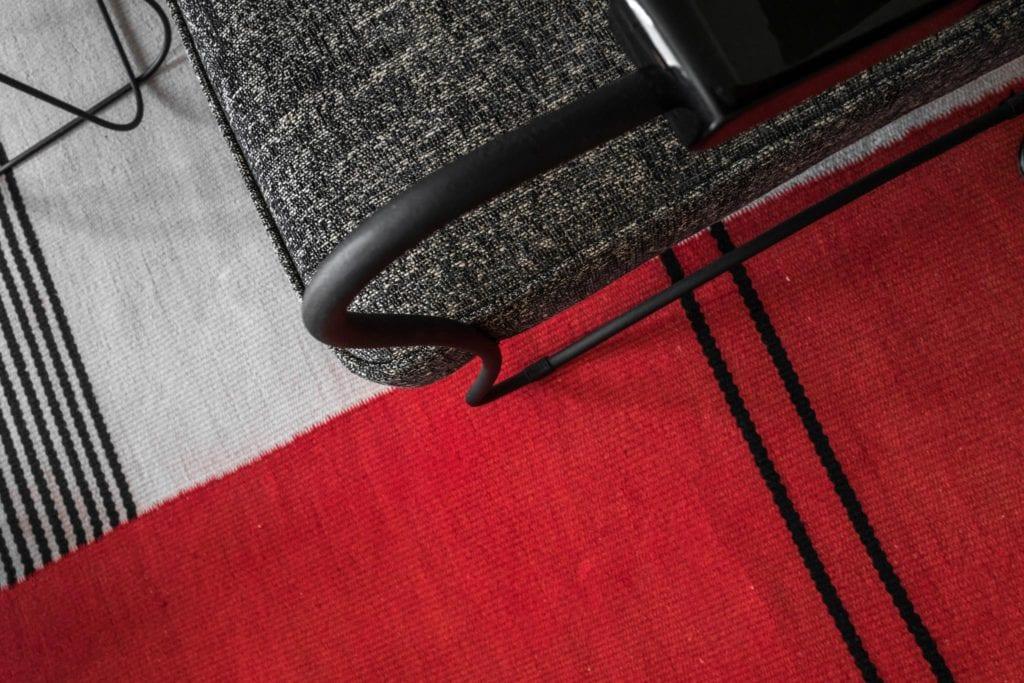 Piękne mieszkanie w zabytkowej kamienicy projektu Loft Kolasiński. Widok z góry na szary fotel i dywan z czerwonym detalem.