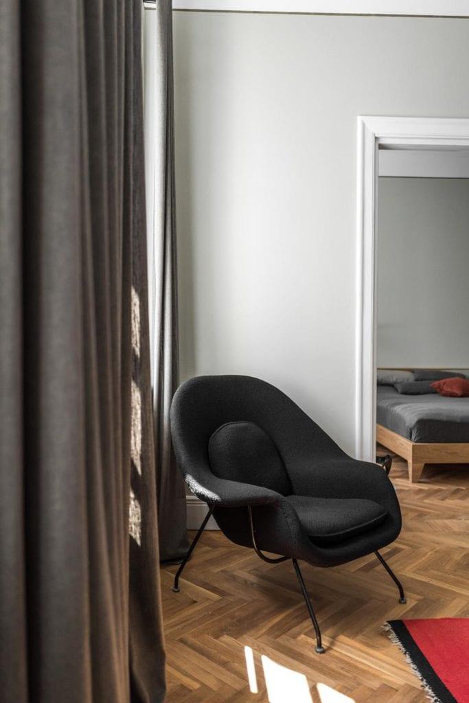 Piękne mieszkanie w zabytkowej kamienicy projektu Loft Kolasiński. Szary fotel stojący w salonie przy ścianie.