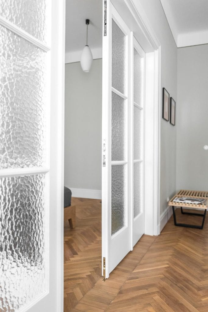 Piękne mieszkanie w zabytkowej kamienicy projektu Loft Kolasiński. Duże białe drzwi dzielące dwa pomieszczenia.