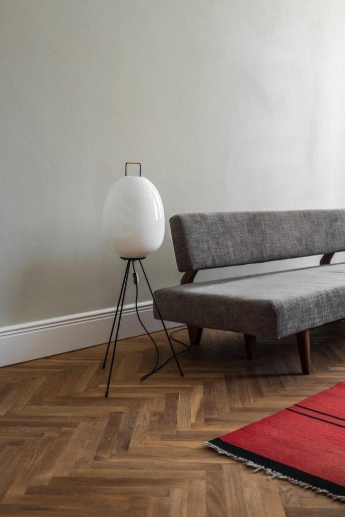 Piękne mieszkanie w zabytkowej kamienicy projektu Loft Kolasiński. Duża, stojąca lampa z białym kloszem w salonie.