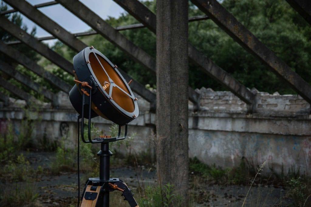 Ciemna lampa Glash projektu Bartosza Dąbrowskiego stojąca w opuszczonym ogrodzie