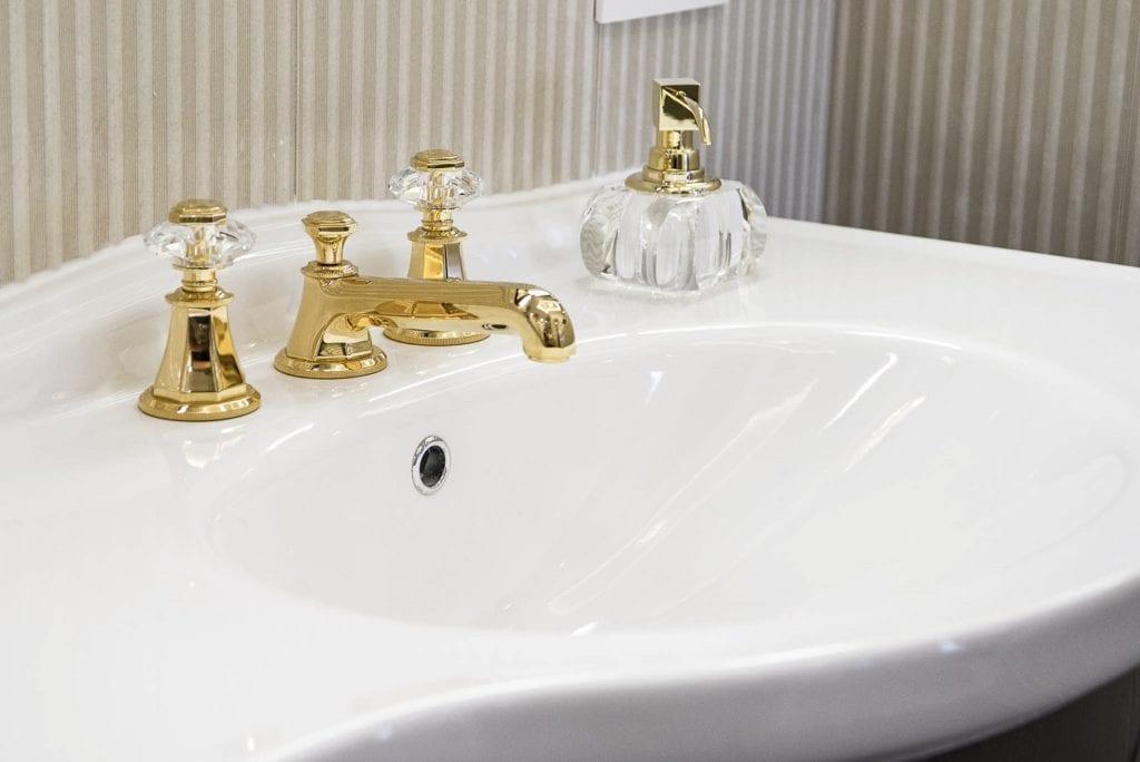 Mango Studio i krakowski apartament Angel Plaza, biała umywalka w łazience, bateria w kolorze złotym