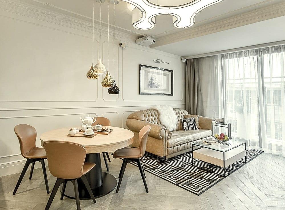 Mango Studio i krakowski apartament Angel Plaza, widok na salon z dużym stołem, czterema krzesłami, sofa i stolik
