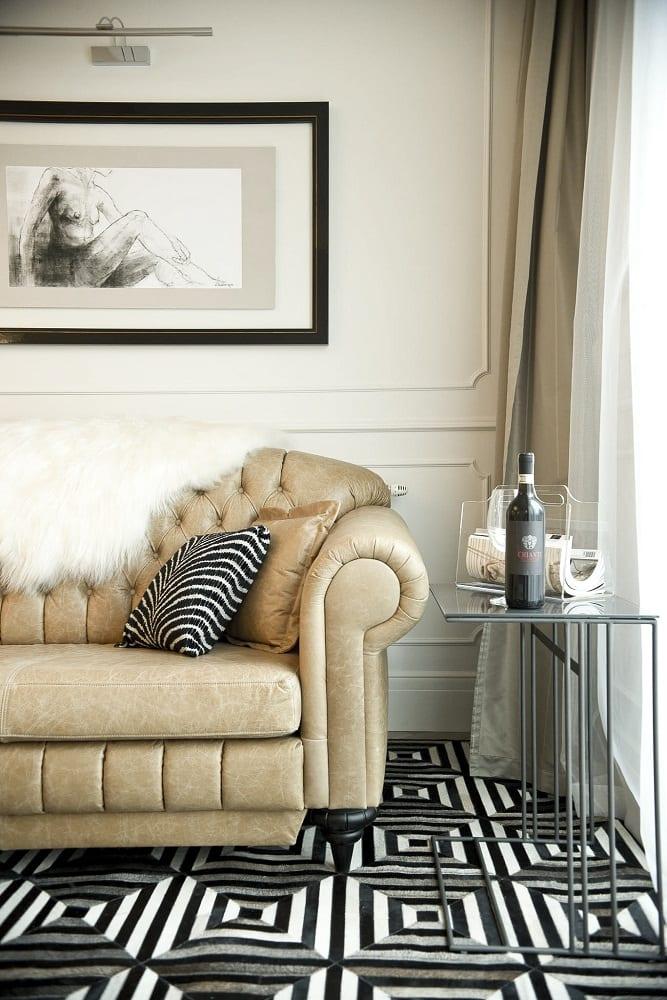 Mango Studio i krakowski apartament Angel Plaza, jasno-brązowa sofa z białym pledem i stolik