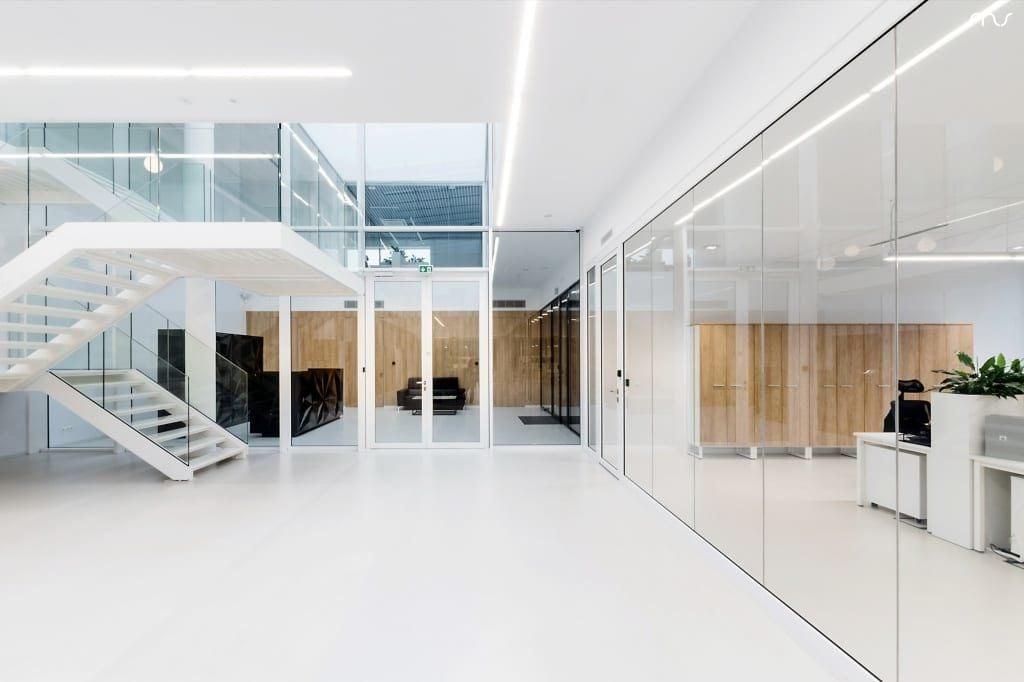 Jasne wnętrze z białą podłogą w siedzibie firmy Pivexin Technology projektu pracowni Mus Architects