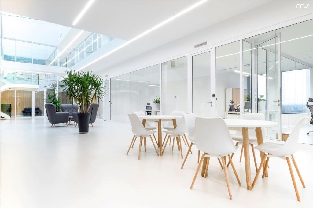 Biały stół z białymi krzesłami w siedzibie firmy Pivexin Technology projektu pracowni Mus Architects