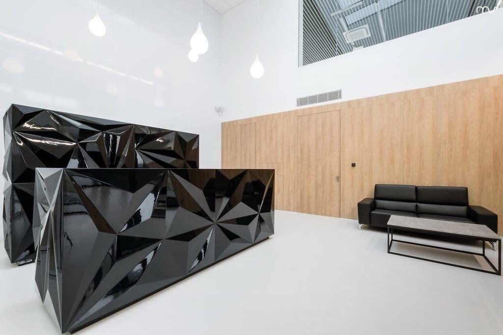 Duża czarna lada na recepcji w siedzibie firmy Pivexin Technology projektu pracowni Mus Architects