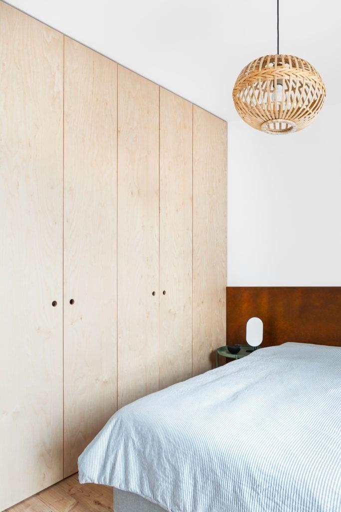 Duża szafa z drzwiami w sypialni w jasnym mieszkaniu projektu Besign Studio