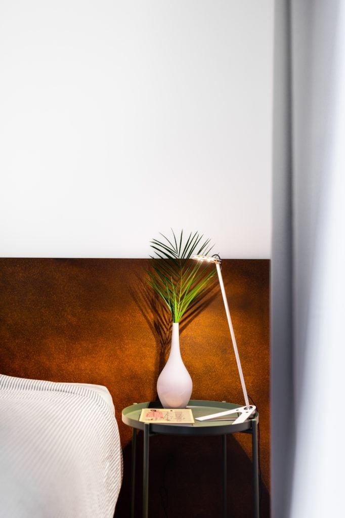 Kwiat w białym wazonie stojący na nocnej szafce przy łóżku