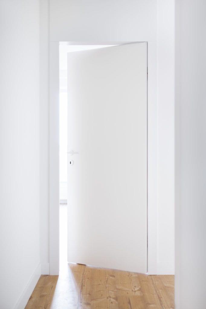 Białe drzwi w jasnym mieszkaniu