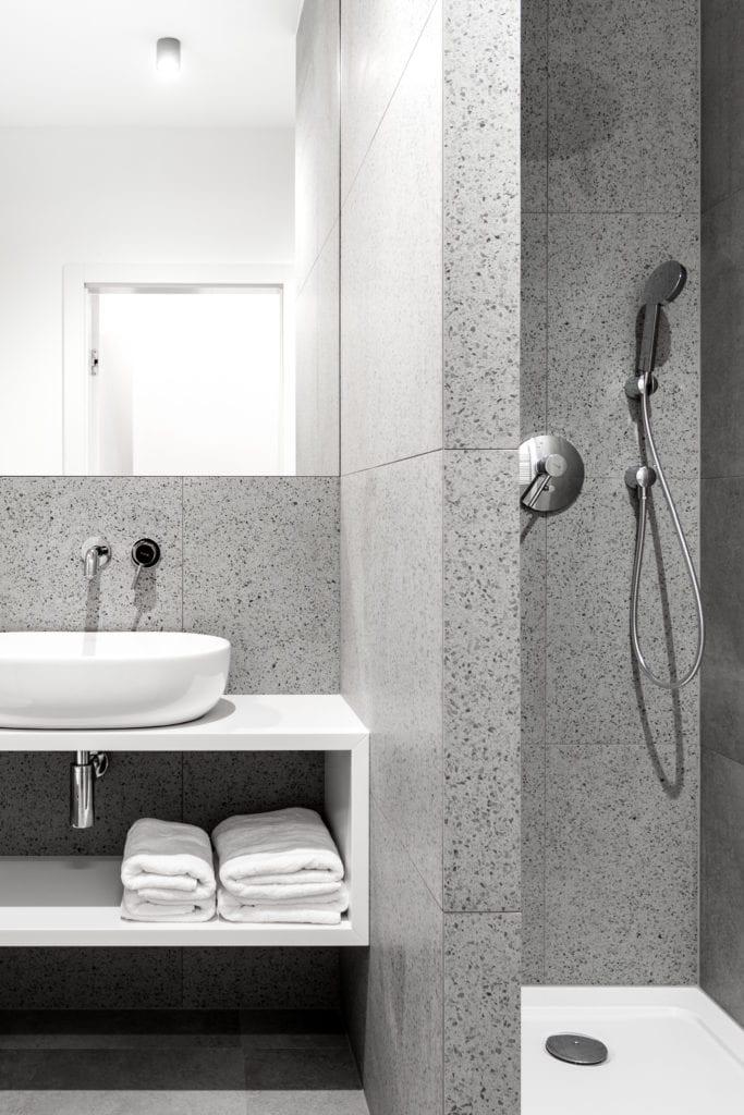 Szara łazienka z dużym lustrem w mieszkaniu projektu Besign Studio