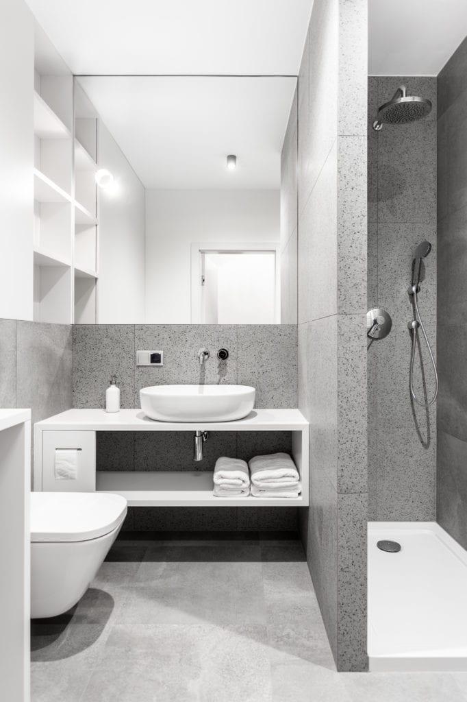 Szara łazienka z dużym lustrem i białymi szafkami